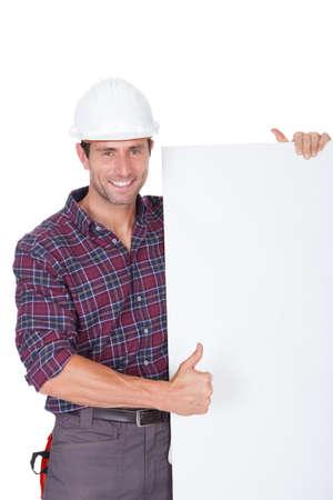 Man Wearing Hard Hat Holding Placard On White Background photo
