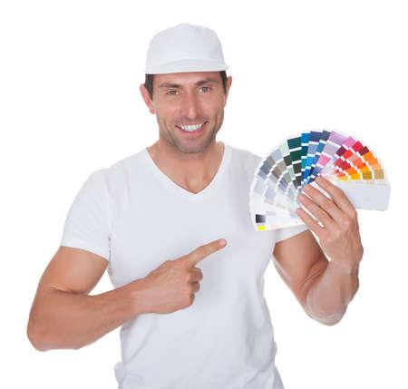 pintora: Pintor que sostiene un rodillo de pintura y el espectro de muestras de color en el fondo blanco