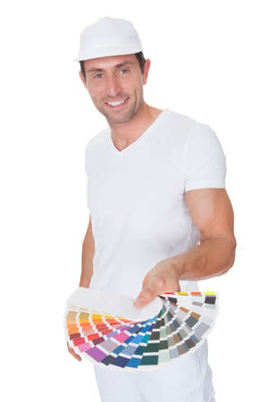 painter and decorator: Painter Holding A Paint Roller And Spectrum Of Color Samples On White Background
