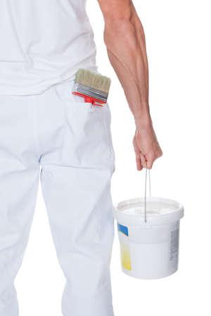 hombre pintando: Pintor que sostiene un rodillo de pintura y cucharón en el fondo blanco
