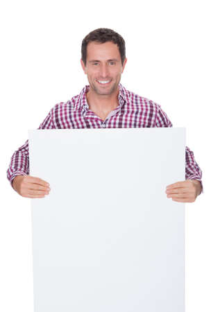 Portrait Of Young Man Holding Placard Isolated On White Background photo