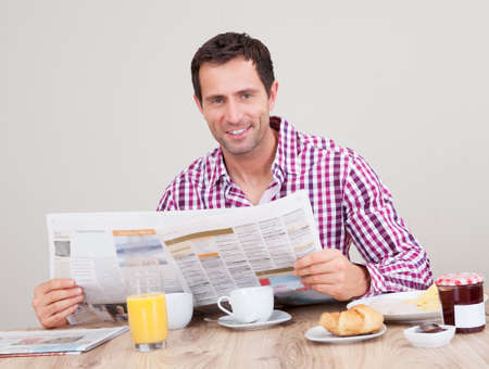 Portrait Of Young Man Reading Newspaper At Breakfast, Indoors photo