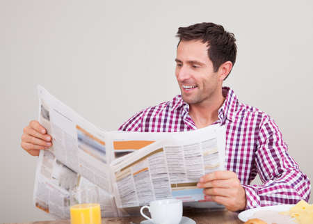 newspaper reading: Portrait Of Young Man Reading Newspaper At Breakfast, Indoors