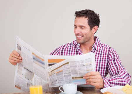 newspapers: Portret Van Jonge Man lezing krant Ontbijt, Indoors