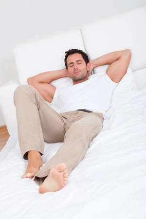 cushion: Portrait Of Young Man Sleeping On Bed In Bedroom Stock Photo