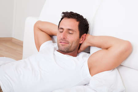 one eye closed: Portrait Of Young Man Sleeping On Bed In Bedroom Stock Photo