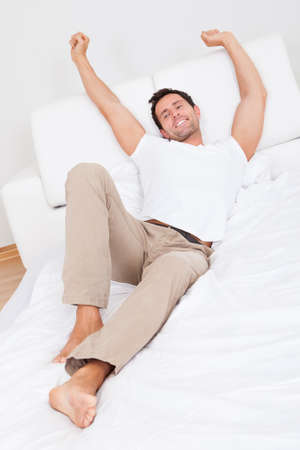 Man Stretching On Bed While Waking Up, Indoors photo