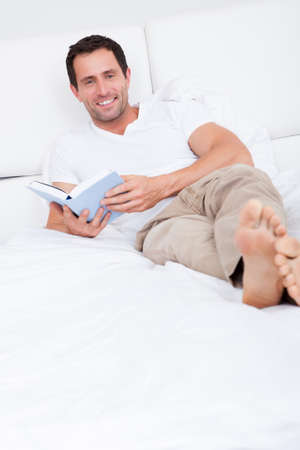 white bed: Portrait Of Young Man Reading Book On Bed, Indoors