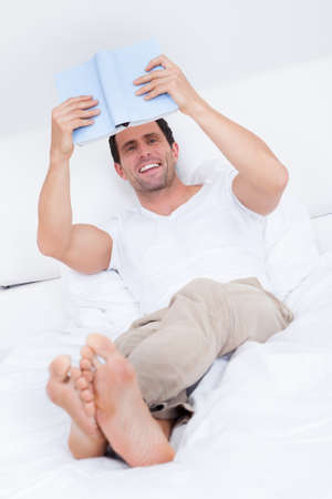 Portrait Of Young Man Reading Book On Bed, Indoors Stock Photo - 15403894