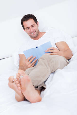 Portrait Of Young Man Reading Book On Bed, Indoors Stock Photo - 15404063