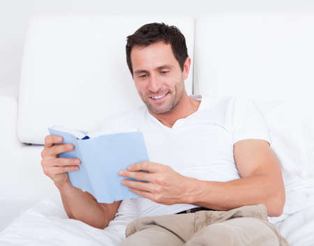 Portrait Of Young Man Reading Book On Bed, Indoors Stock Photo - 15404129