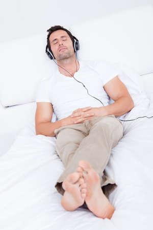 pies masculinos: El hombre joven escucha música en auriculares, Interior