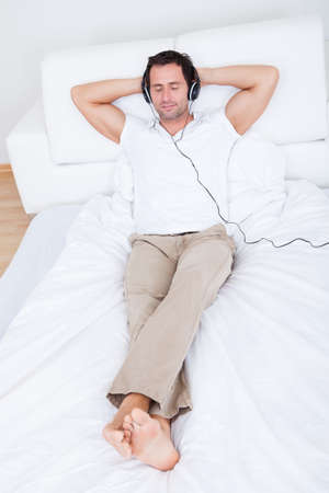 Young Man Listening Music On Headphone, Indoors photo