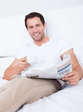 Young Man Holding Cup In Hand Reading Newspaper, Indoors Stock Photo - 15404114