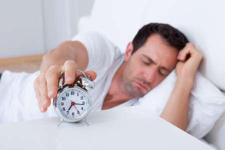 obudził: Wyczerpana człowiek jest obudzony przez budzik w swojej sypialni
