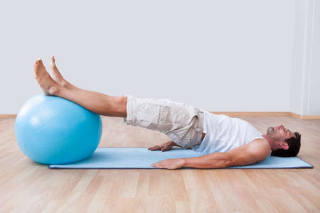 fit ball: Young Man Exercising On A Pilates Ball, Indoors Stock Photo