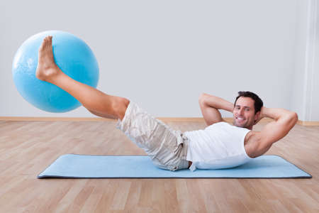 Young Man Exercising On A Pilates Ball, Indoors photo