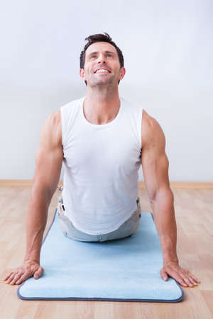 Young Man Exercising On Exercise Mat, Indoors Stock Photo - 15404055
