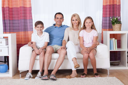 family sofa: A Happy Family With Two Children Sitting On Sofa At Home