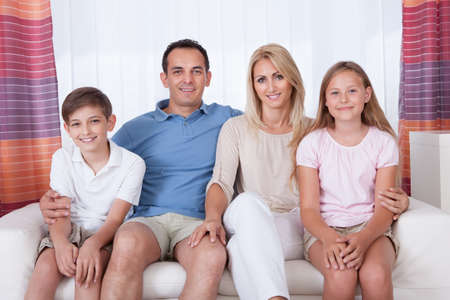 A Happy Family With Two Children Sitting On Sofa At Home photo
