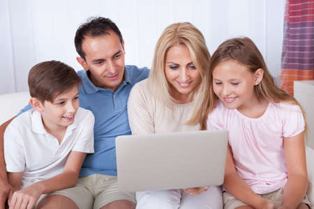 A Happy Family With Two Children Sitting On A Sofa Using Laptop At Home Stock Photo - 15574920