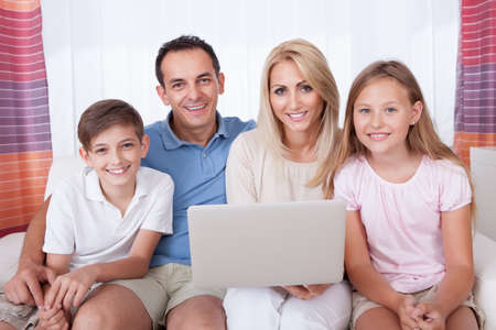 A Happy Family With Two Children Sitting On A Sofa Using Laptop At Home Stock Photo - 15574900