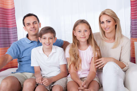 A Happy Family With Two Children Sitting On Sofa At Home Stock Photo - 15574886