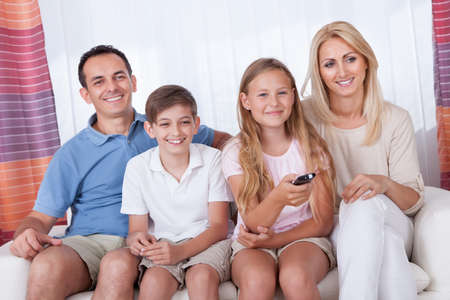 A Happy Family With Two Children Sitting On A Sofa Watching Tv At Home photo