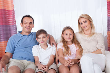 A Happy Family With Two Children Sitting On Sofa At Home Stock Photo - 15574921