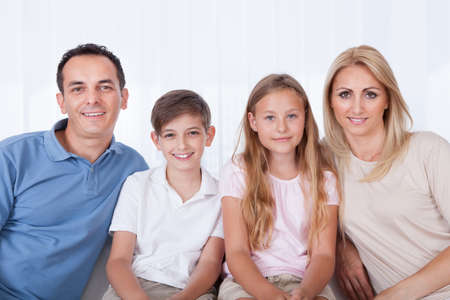 A Happy Family With Two Children Sitting On Sofa At Home Stock Photo - 15574923