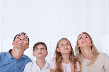 Portrait Of Familie mit zwei Kindern Looking Up, Innenaufnahme