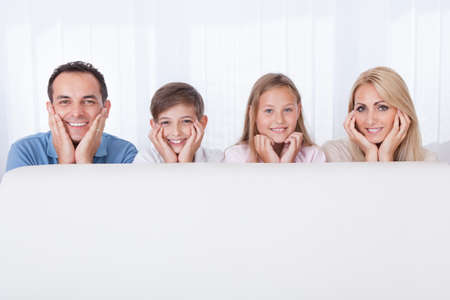 Portrait Of  Happy Family Behind White Sofa, Indoors photo