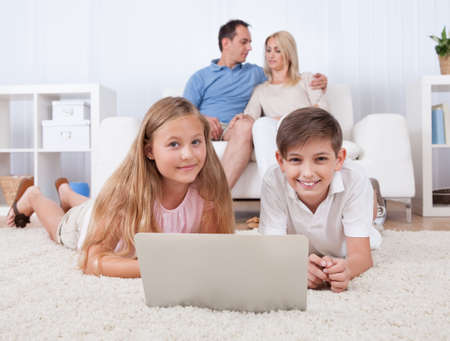 Children On The Carpet Using Tablet And Laptop With Parents Behind Them At Home photo