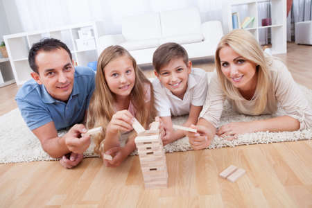 Happy Family Laying On Carpet Playing With The Wooden Blocks At Home Stock Photo - 15574882