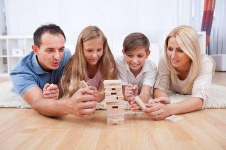 hermanos jugando: Familia feliz que pone en la alfombra jugando con los bloques de madera At Home