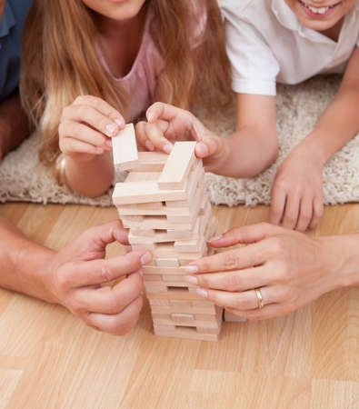 Happy Family Laying On Carpet Playing With The Wooden Blocks At Home photo