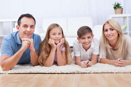 family on couch: Portrait Of Happy Family With Two Children Laying On Carpet At Home