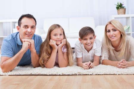 Retrato de la familia feliz con dos hijos que pone en la alfombra en el hogar