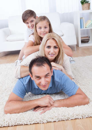 familias unidas: Familia feliz con dos niños que mienten en la alfombra colmada en el salón en el hogar Foto de archivo