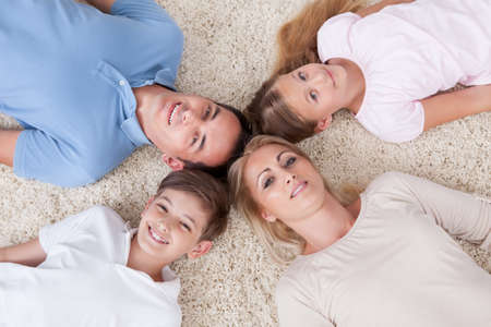 family looking up: Close-up Of Happy Family Lying On Carpet Looking Up Heads Together At Home