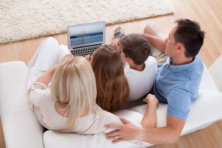 elevated view: A Happy Family With Two Children Sitting On A Sofa Using Laptop At Home Stock Photo