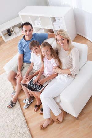 bambini seduti: Una famiglia felice con due figli seduti su un divano con laptop a casa