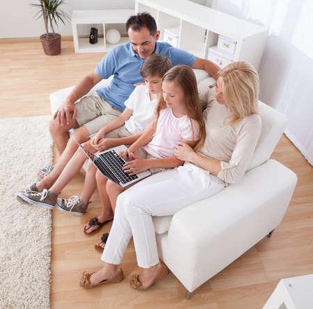 A boldog család, két gyermek ül egy kanapén használata laptop otthon Stock fotó