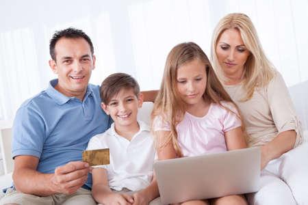 Eine gl�ckliche Familie mit zwei Kindern auf einem Sofa sitzend Einkaufen mit Laptop zu Hause Lizenzfreie Bilder