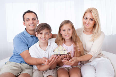 family on couch: Family With Two Children Sitting On Couch Holding Miniature Model Of House At Home Stock Photo