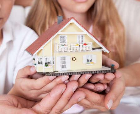 Dream Home: Familie mit zwei Kindern sitzt auf der Couch Holding-Miniaturmodell House At Home Lizenzfreie Bilder