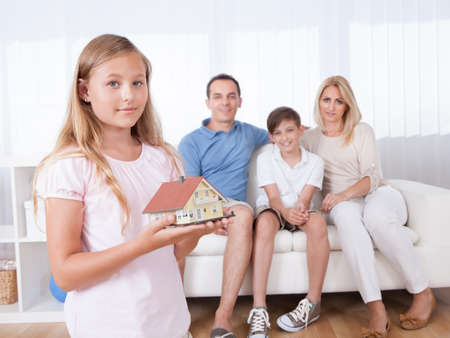 model home: Girl Holding Miniature Model Of House In Front Of Parent And Brother Sitting On Couch, Indoors Stock Photo