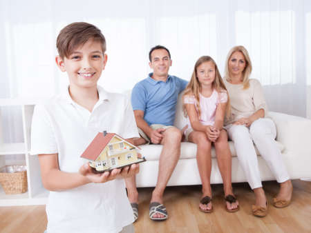 Boy Holding Miniature Model Of House In Front Of Parent And Sister Sitting On Couch, Indoors photo