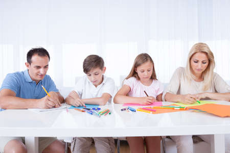 Young Family Drawing Together With Colorful Pencils And Crayons At Home photo