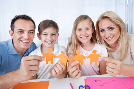 four person: Portrait Of Happy Family Holding Paper People In Hand At Home Stock Photo